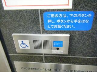 押しボタン全体の画像。すぐ上に「ご用の方は、下のボタンを押し、ボタンから手をはなしてお話ください。」と書かれた貼り紙があります。
